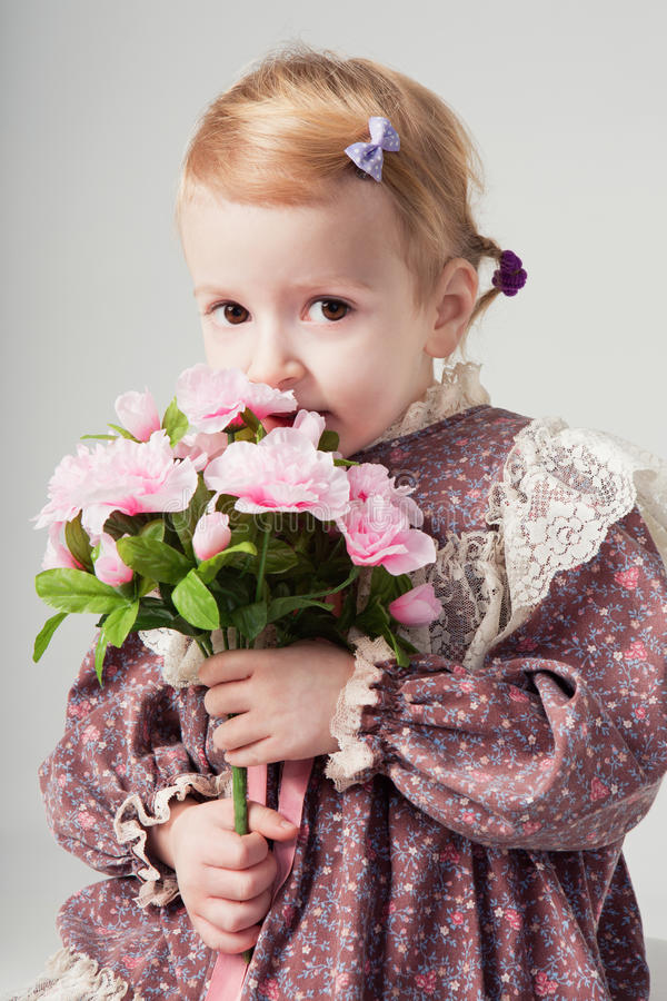 Beautiful little girl in retro dress with bouquet of flowers. Cute girl is smelling flowers. Studio shot. Gray background. Greeting Card stock photos