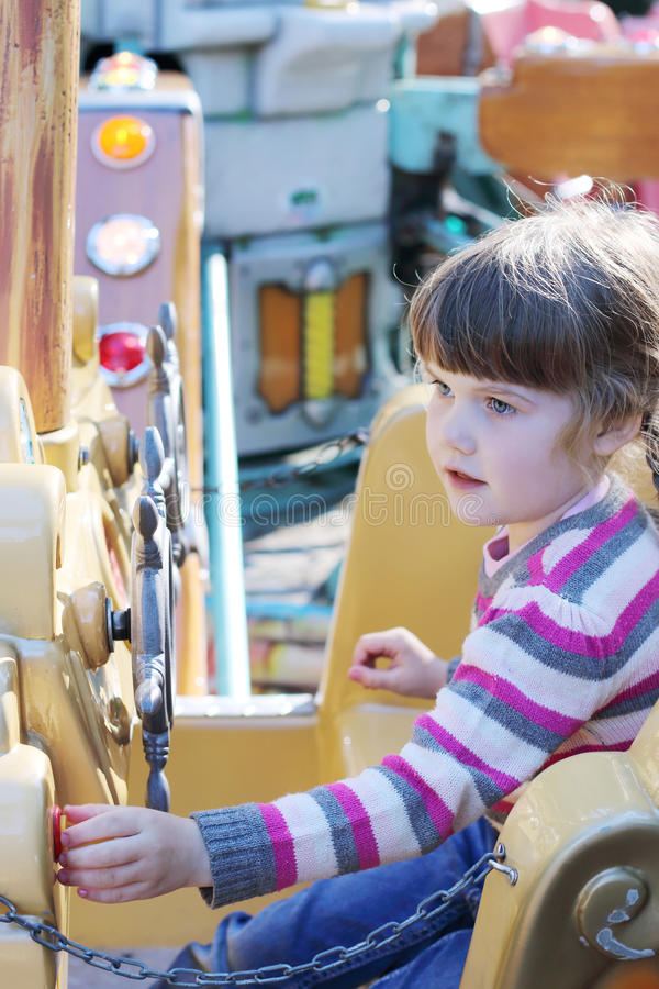 Beautiful little girl rides on carousel pirate ship. In summer park stock image