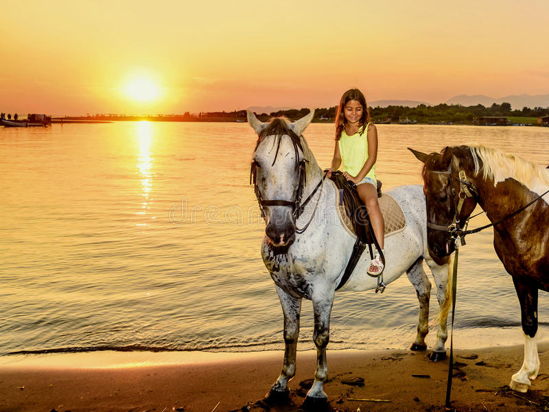Beautiful little girl riding horse in sunset by the sea on the royalty free stock image