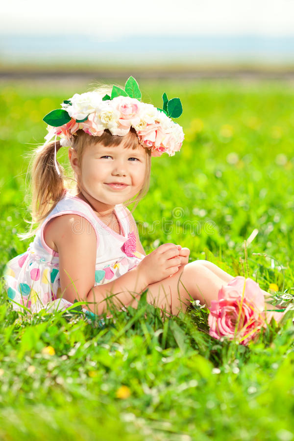 Beautiful little girl with a rose in his hand and a wreath of roses on her head in a field stock photography