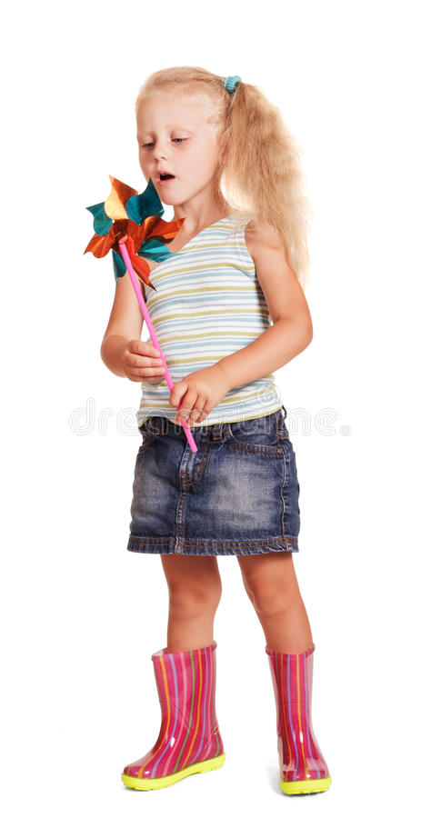 Beautiful little girl in rubber boots blowing plastic windmill isolated. stock images