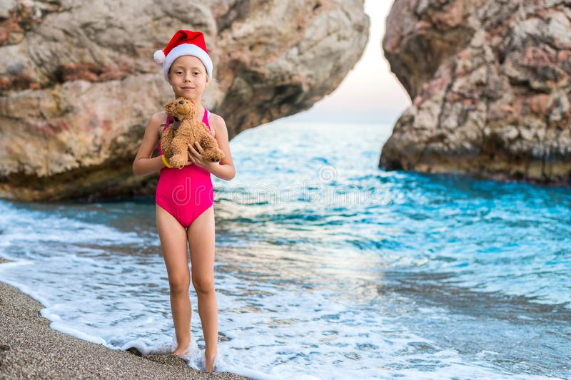 Beautiful little girl in a Santa Claus hat celebrating New Year on the beach. stock photo