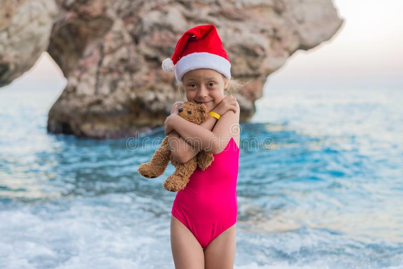 Beautiful little girl in a Santa Claus hat celebrating New Year on the beach. stock photos