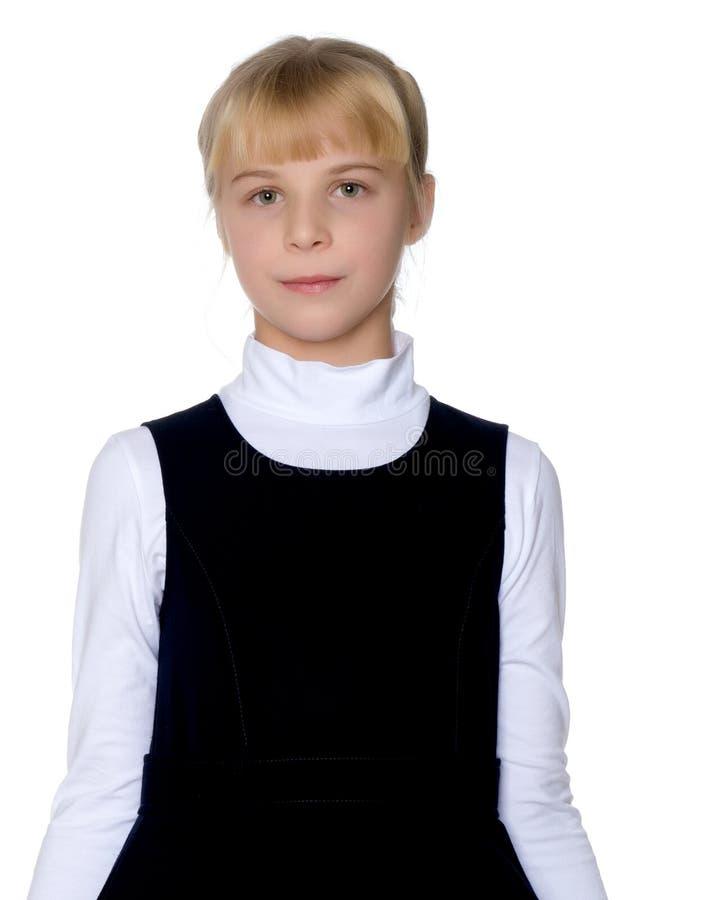 Beautiful little girl in a school uniform. royalty free stock photos