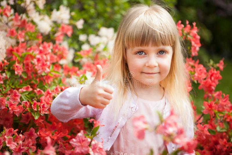 Beautiful little girl show thumb up outdoors and smile royalty free stock images