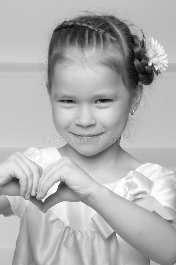 Little girl shows heart with her hands. royalty free stock image