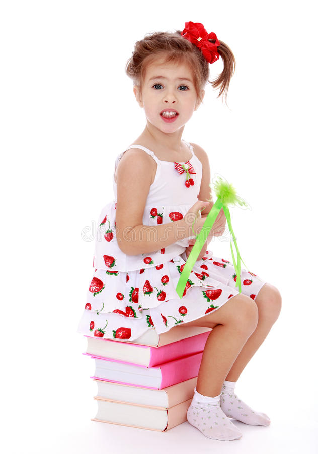 Beautiful Little Girl Sitting On Colorful Books In Stock