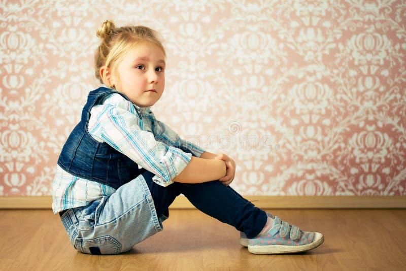 Beautiful little girl sitting on floor stock photo