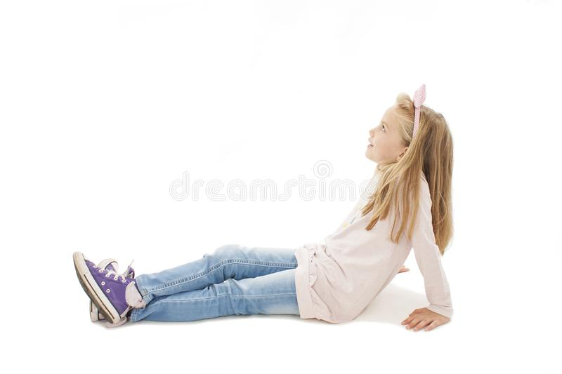 Beautiful little girl sitting on floor, looking on copy space royalty free stock photography