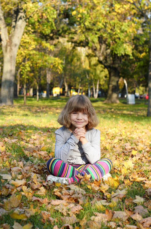 Download Beautiful Little Girl Sitting In Park Stock Photo - Image: 27435940