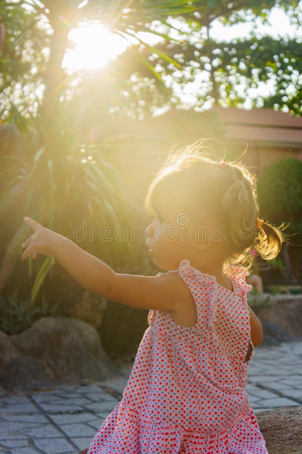 Beautiful little girl is sitting on a rock the sunset. towers Ponagar. Vietnam. royalty free stock photo