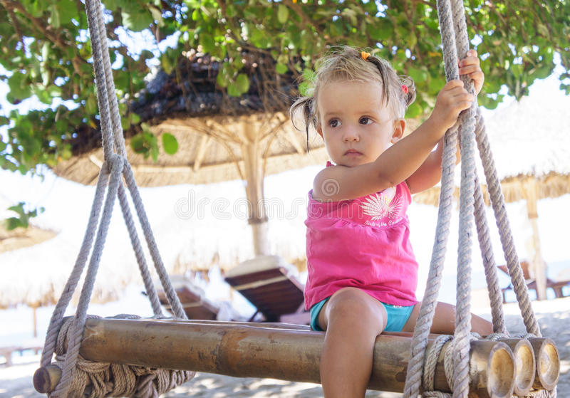 Beautiful little girl sitting rope swings on the beach. royalty free stock image