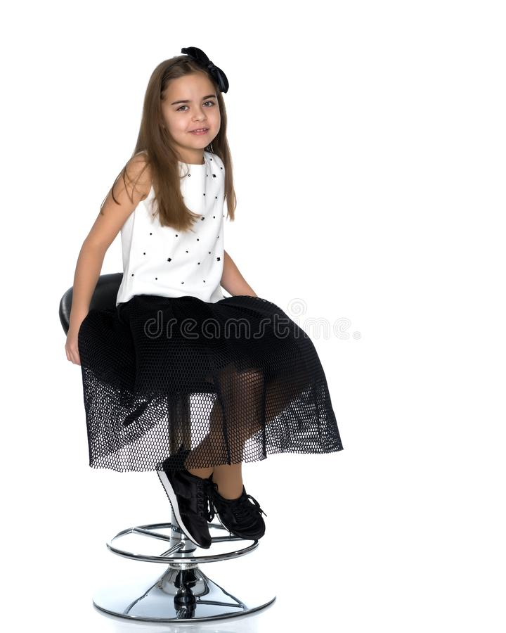 Little girl is sitting on a chair royalty free stock photography
