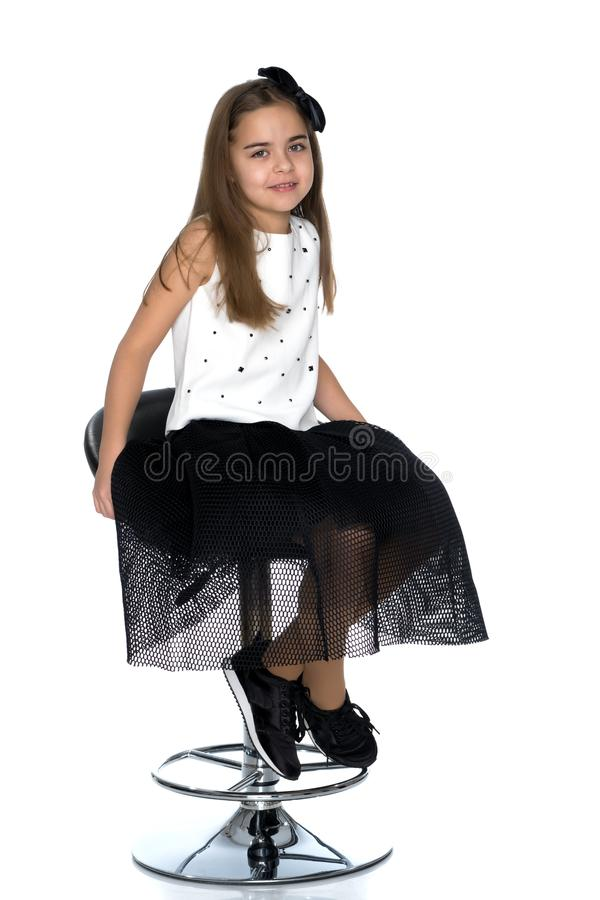 Little girl is sitting on a chair. Beautiful little girl is sitting on a swivel chair. The concept of style and fashion, children`s emotions. Isolated on white stock images
