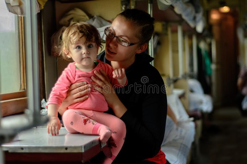 A young mother travels in glasses along with a wonderfully beautiful daughter stock photography