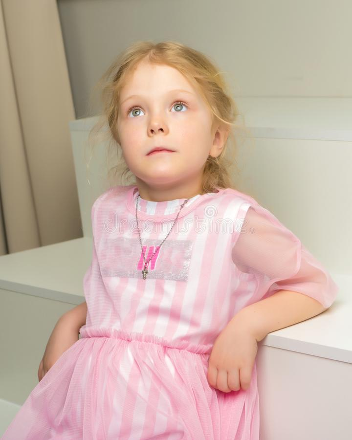 Beautiful little girl is sitting on the white staircase. royalty free stock images