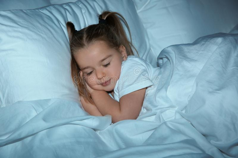 Beautiful little girl sleeping in bed at night. Bedtime stock photography
