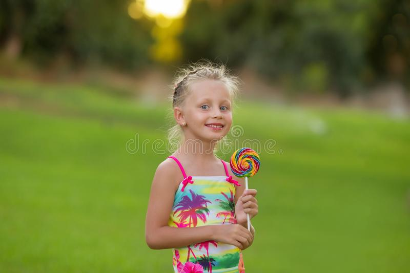 Beautiful little girl with smiling eyes with colored lollipop. Summertime stock images