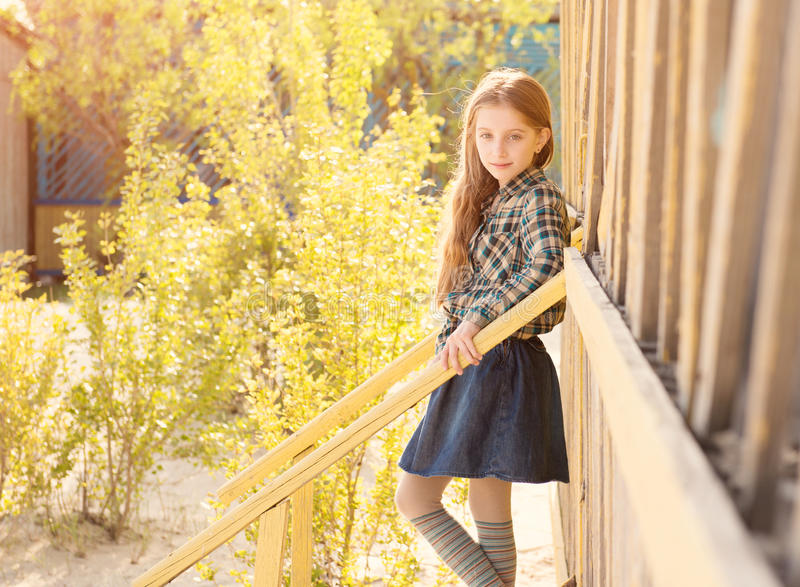 Beautiful little girl on stairs of wooden house. On sunny day stock images