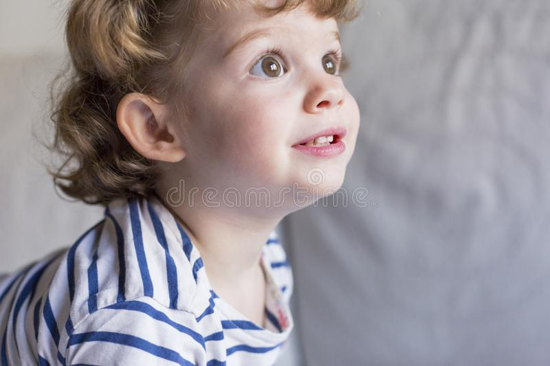beautiful little girl standing on bed and smiling. Fun, home, indoors. Lifestyle stock image