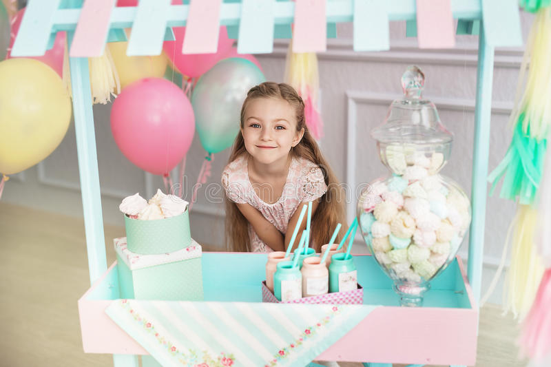 Beautiful little girl stands behind the toy candy shop. A beautiful little girl stands behind the toy candy shop royalty free stock images
