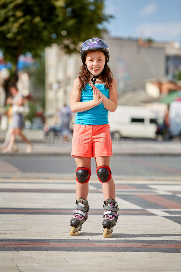 Beautiful little girl stands in roller skates at a city park in the sunshiny summer day. Cute sportive girld dressed in the colorful sportwear, with helmet and stock photo