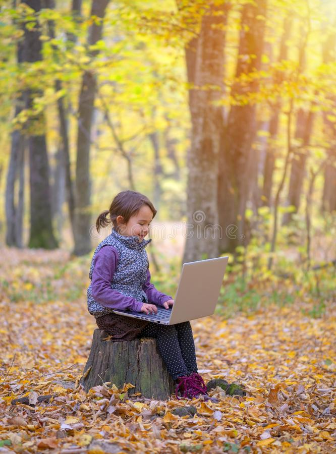 Beautiful little girl stands on a trunk of tree smiling royalty free stock photos