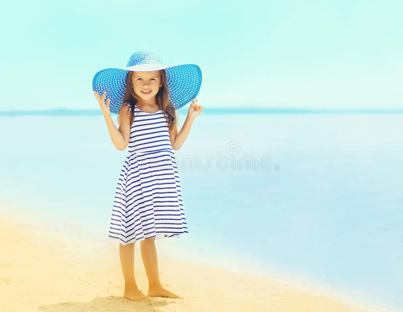 Beautiful little girl in a striped dress and summer straw hat relaxing on the beach near sea royalty free stock image
