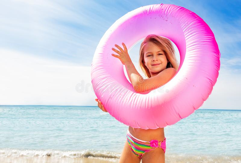 Beautiful little girl with swim ring on the beach. Portrait of beautiful little girl looking through the pink swim ring on the beach royalty free stock images