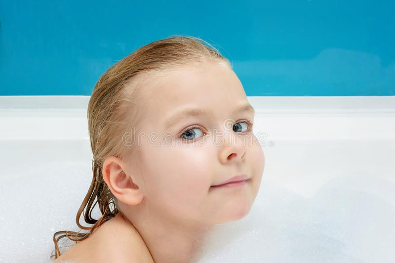 A beautiful, little girl swims in a bath with foam. Cute smiling baby. royalty free stock image