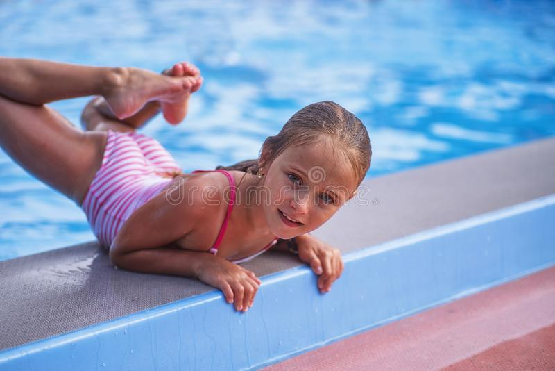 Beautiful little girl swims in the pool , cute little girl in pool in sunny day. stock photography