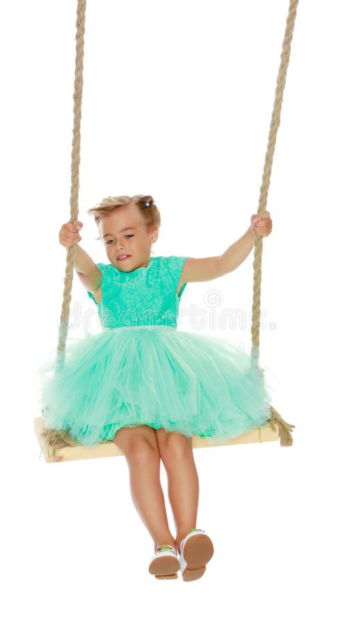 Little girl swinging on a swing royalty free stock photography