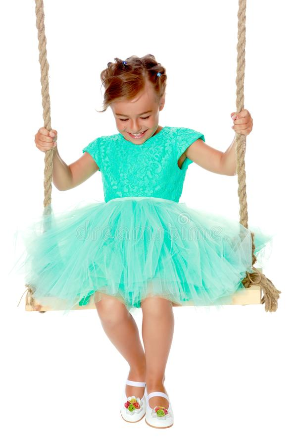 Little girl swinging on a swing stock photography