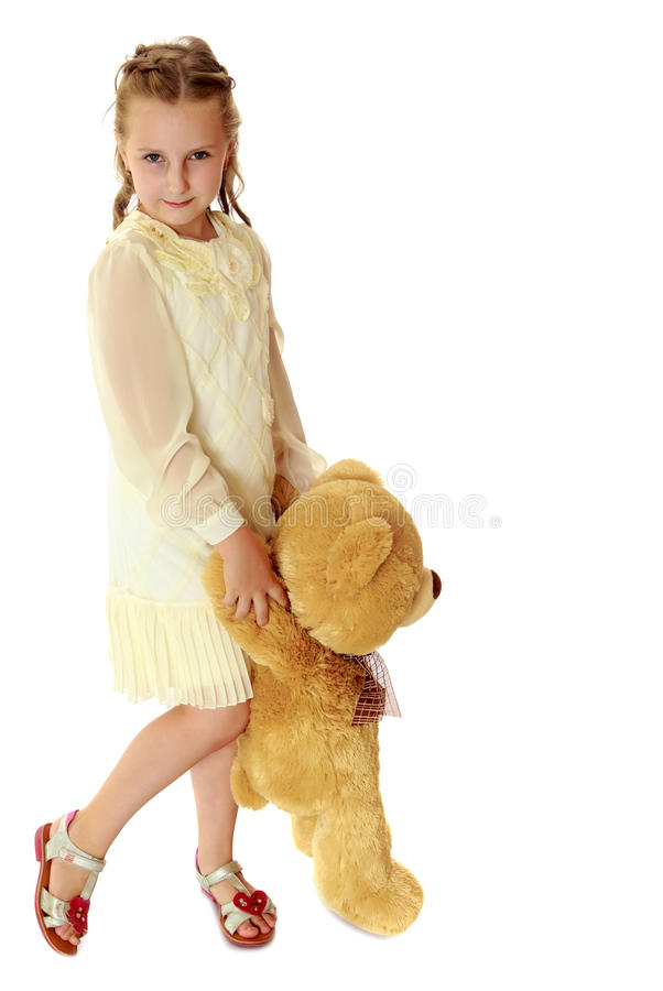 Beautiful little girl with a Teddy bear. Beautiful little girl in stylish white dress, holding a Teddy bear. Full growth.Isolated on white background royalty free stock image