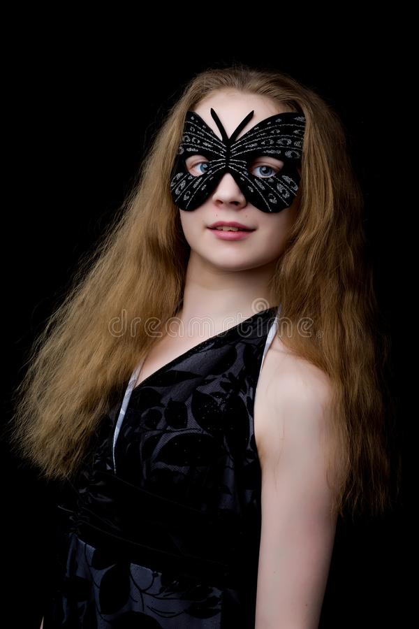 Beautiful little girl in theatrical mask. On a black background. royalty free stock photo