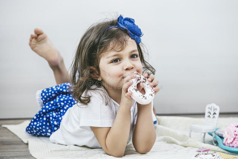 Beautiful little girl with toy dishes, sweets and dolls is playing at the tea party stock photo