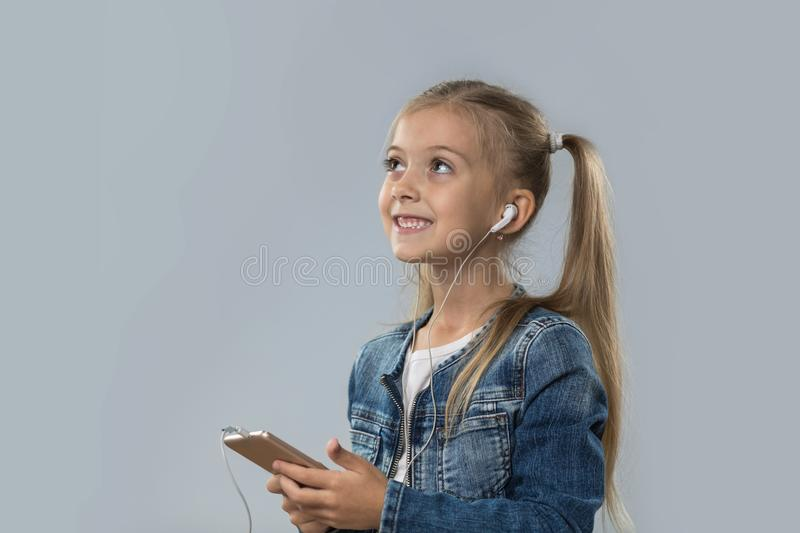 Beautiful Little Girl Using Smart Phone Listen Music Wear Earphones Happy Smiling Look To Copy Space Isolated royalty free stock photography