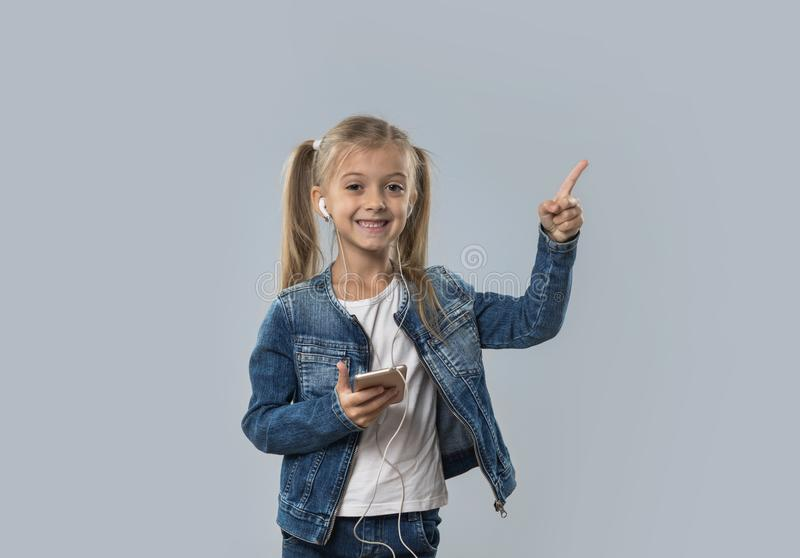 Beautiful Little Girl Using Smart Phone Listen Music Wear Earphones Happy Smiling Point To Copy Space Isolated royalty free stock photos