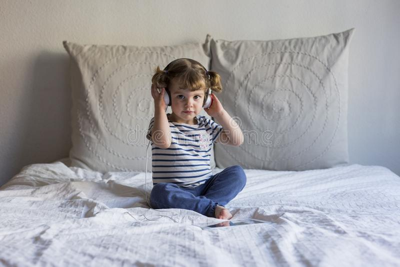 Beautiful little girl using tablet and listening to music on headset on bed. Home, indoors. LIfestyle royalty free stock photos