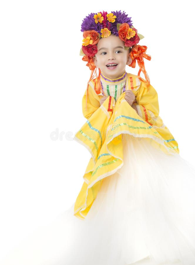 Traditional Mexican dress and hair piece. Beautiful little girl wearing colorful traditional Mexican dress and hair piece, white background stock image