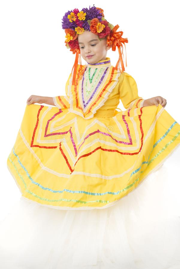 Traditional Mexican dress and hair piece. Beautiful little girl wearing colorful traditional Mexican dress and hair piece, white background royalty free stock photo