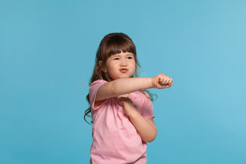 Beautiful little girl wearing in a pink t-shirt is posing against a blue studio background. stock images