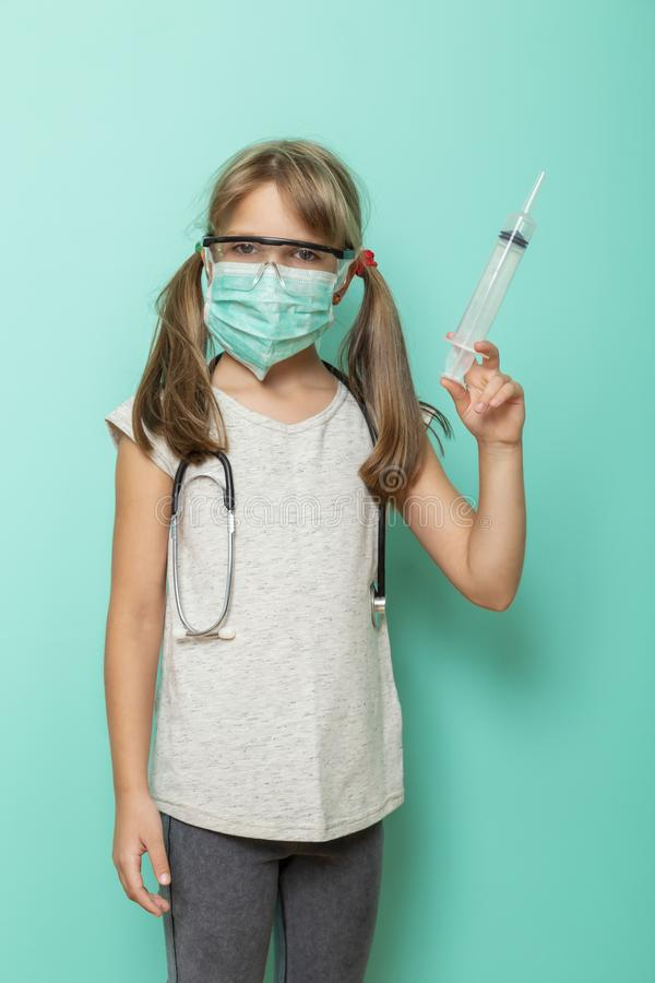 Child role-playing a doctor. Beautiful little girl wearing surgical mask, stethoscope and protective lab glasses holding a giant syringe; child role-playing a royalty free stock photography