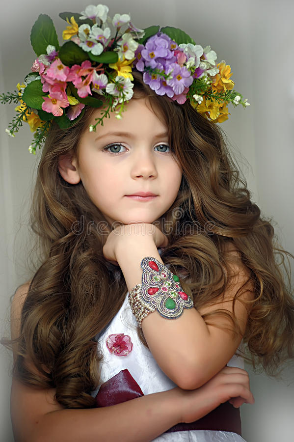Beautiful little girl wearing a wreath of flowers. And a bracelet on her arm, studio photo royalty free stock photos