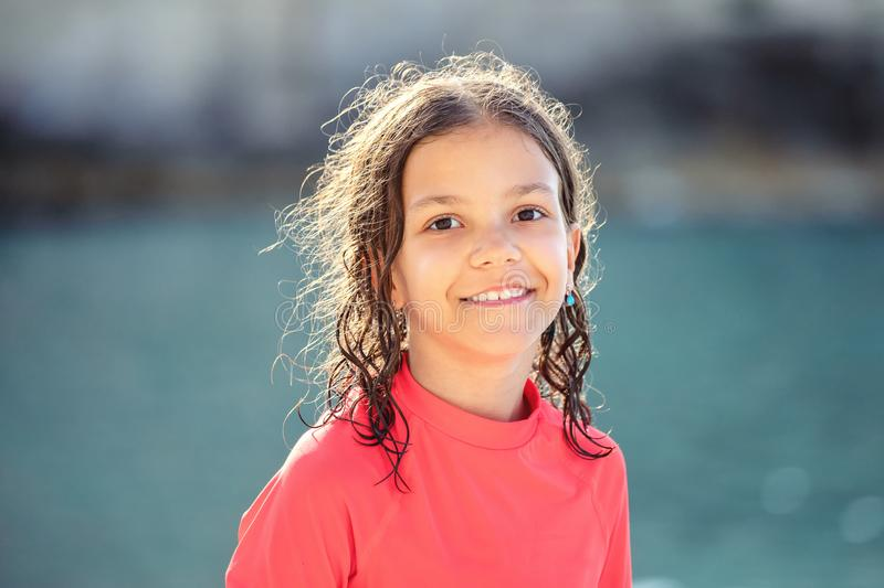 Beautiful little girl with wet hair smiling and looking at camera at beach during sunset, Outdoor portrait of happy child royalty free stock photo