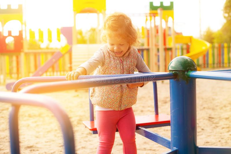Beautiful little girl whirls on the merry go round in the childrens park in warm sunny weather royalty free stock image