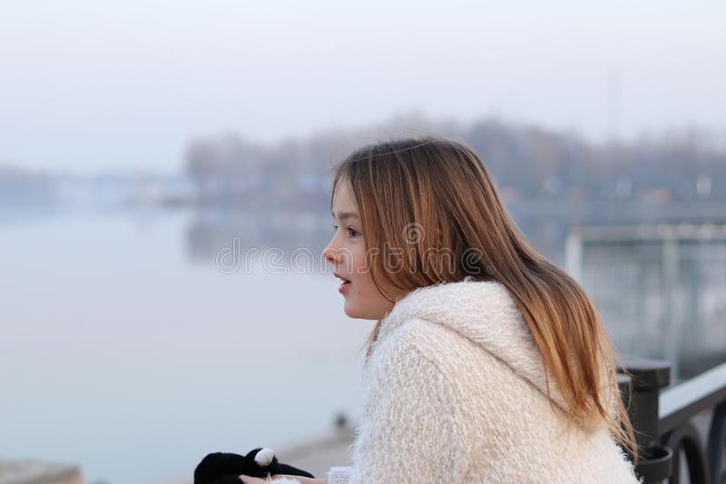 Beautiful little girl in white coat looking at the river, surprised royalty free stock image