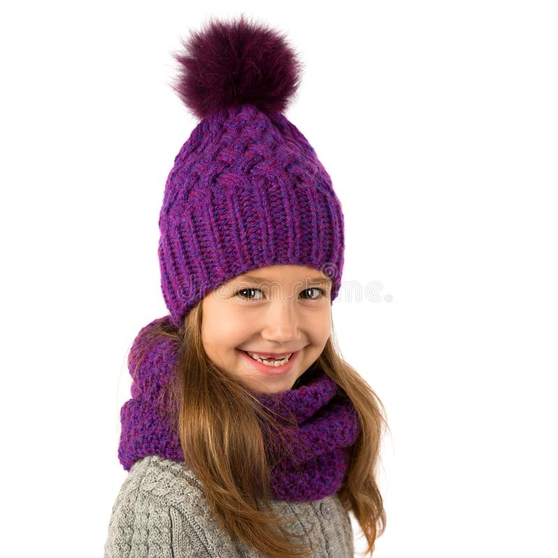 Beautiful little girl in winter warm purple hat and scarf on white. Children winter clothes. Beautiful little girl in winter warm purple hat and scarf on a white royalty free stock photo