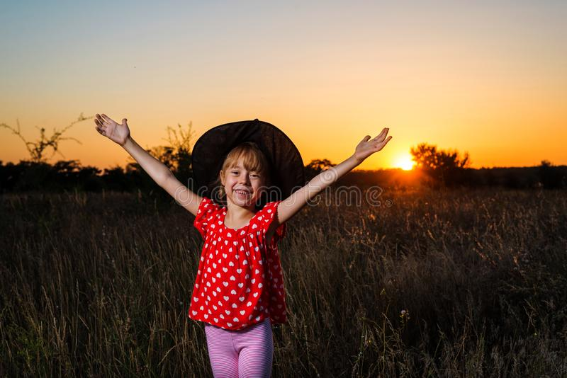 Beautiful little girl in witch costume on sunset background, free space. royalty free stock photos