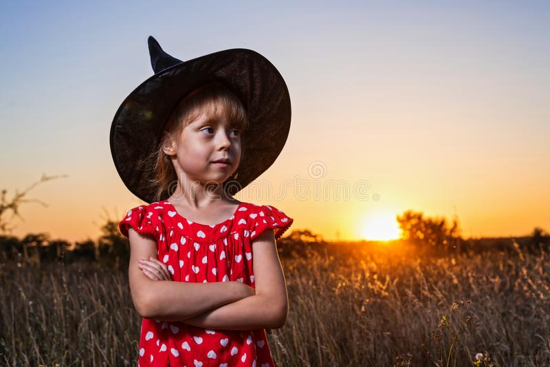 Beautiful little girl in witch costume on sunset background, free space. royalty free stock images